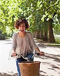 Exuberant woman with mouth open riding bicycle in park Stock Photo - Premium Royalty-Free, Artist: Blend Images, Code: 635-05656322