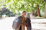 Couple with umbrella kissing in sunny park Stock Photo - Premium Royalty-Freenull, Code: 635-05656325