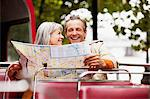 Smiling couple looking at map on double decker bus Stock Photo - Premium Royalty-Freenull, Code: 635-05656342