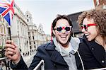 Portrait of exuberant couple with British flag and sunglasses riding double decker bus Stock Photo - Premium Royalty-Freenull, Code: 635-05656346