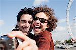 Happy couple taking self-portrait with digital camera near ferris wheel Stock Photo - Premium Royalty-Free, Artist: Blend Images, Code: 635-05656348