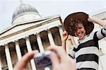 Man photographing woman with hat in front of historical landmark Stock Photo - Premium Royalty-Freenull, Code: 635-05656351