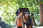 Couple sharing umbrella in sunny park Stock Photo - Premium Royalty-Freenull, Code: 635-05656366