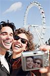 Happy couple taking self-portrait with digital camera in front of ferris wheel Stock Photo - Premium Royalty-Free, Artist: ableimages, Code: 635-05656380