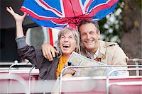 Wind flipping British flag umbrella over happy couple with map on double decker bus Stock Photo - Premium Royalty-Freenull, Code: 635-05656383