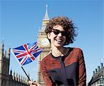 Portrait of smiling woman with British flag in front of Big Ben clocktower Stock Photo - Premium Royalty-Freenull, Code: 635-05656387
