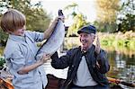 Grandson catching fish with grandfather cheering in background Stock Photo - Premium Royalty-Freenull, Code: 635-05656406