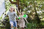 Mother and daughter running with bubble wands in park Stock Photo - Premium Royalty-Freenull, Code: 635-05656413