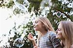 Mother and daughter blowing bubbles under tree Stock Photo - Premium Royalty-Freenull, Code: 635-05656422
