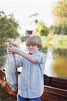 Boy making a face and holding fish in front of lake Stock Photo - Premium Royalty-Freenull, Code: 635-05656423