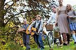 Multi-generation family with guitar and bicycle in apple orchard