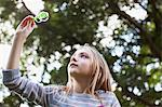Girl holding bubble wand under tree Stock Photo - Premium Royalty-Freenull, Code: 635-05656432