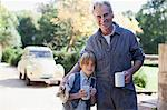 Portrait of smiling grandfather and grandson hugging with coffee mugs in driveway Stock Photo - Premium Royalty-Freenull, Code: 635-05656446