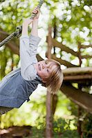 Portrait of boy hanging from rope swing Stock Photo - Premium Royalty-Freenull, Code: 635-05656450