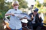 Grandson holding fish with grandfather clapping in background Stock Photo - Premium Royalty-Freenull, Code: 635-05656458