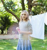 Portrait of smiling girl blowing bubbles in backyard Stock Photo - Premium Royalty-Freenull, Code: 635-05656461
