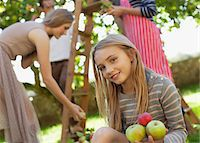 Portrait of smiling girl holding apples in orchard Stock Photo - Premium Royalty-Freenull, Code: 635-05656464