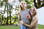 Portrait of smiling sisters blowing bubbles in backyard Stock Photo - Premium Royalty-Free, Artist: Blend Images, Code: 635-05656468