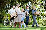 Multi-generation family with bicycle, apples and guitar in orchard