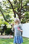 Girl blowing bubbles in backyard Stock Photo - Premium Royalty-Freenull, Code: 635-05656484
