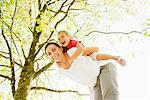 Mother piggybacking daughter under tree Stock Photo - Premium Royalty-Freenull, Code: 635-05656511