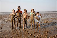 Children covered in mud on rocky beach Stock Photo - Premium Royalty-Freenull, Code: 649-05656908