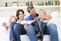 Family relaxing together on couch Stock Photo - Premium Royalty-Freenull, Code: 649-05657197