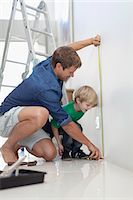 Father and son measuring wall Stock Photo - Premium Royalty-Freenull, Code: 649-05657205