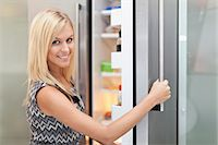 fridge - Woman reaching into fridge Stock Photo - Premium Royalty-Freenull, Code: 649-05657253