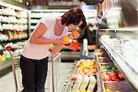 smelly - Woman smelling fruit at grocery store Stock Photo - Premium Royalty-Freenull, Code: 649-05657455