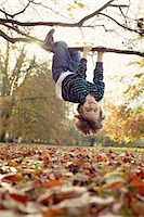 Boy playing on tree outdoors Stock Photo - Premium Royalty-Freenull, Code: 649-05657651