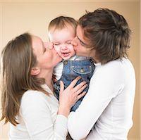 Parents kissing smiling toddler Stock Photo - Premium Royalty-Freenull, Code: 649-05657920