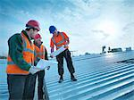 Workers reading blueprints on roof Stock Photo - Premium Royalty-Free, Artist: Blend Images, Code: 649-05657939