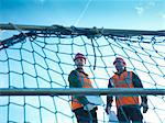 Workers standing behind fence netting Stock Photo - Premium Royalty-Free, Artist: Blend Images, Code: 649-05657947