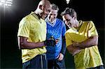 Soccer players looking at cellphone on pitch Stock Photo - Premium Royalty-Freenull, Code: 614-05662291