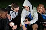 Soccer players looking at cellphone on pitch Stock Photo - Premium Royalty-Freenull, Code: 614-05662297