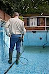 Man Cleaning Swimming Pool with Pressure Washer Stock Photo - Premium Rights-Managed, Artist: Steve McDonough, Code: 700-05662375