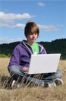 Boy Sitting in Field using Laptop Computer, Blandas, Gard, France Stock Photo - Premium Royalty-Freenull, Code: 600-05662602