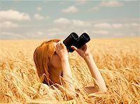 Redhead girl with binocular at wheat field. Stock Photo - Royalty-Freenull, Code: 400-05663689