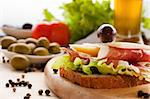 Prosciutto and cheese sandwich with olives and lettuce.Focus is on the cheese. Shallow depth of field. Stock Photo - Royalty-Free, Artist: mythja                        , Code: 400-05666519