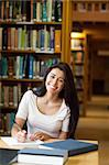 Portrait of a smiling student writing a paper in the library Stock Photo - Royalty-Free, Artist: 4774344sean                   , Code: 400-05668897