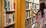 Young woman choosing a book in a library Stock Photo - Royalty-Free, Artist: 4774344sean                   , Code: 400-05668931