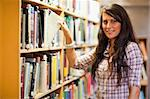 Student choosing a book while looking at the camera Stock Photo - Royalty-Free, Artist: 4774344sean                   , Code: 400-05668933