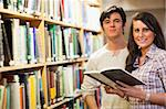 Young students holding a book in a library Stock Photo - Royalty-Free, Artist: 4774344sean                   , Code: 400-05668942