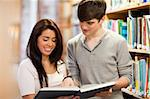 Happy students looking at a book in a library Stock Photo - Royalty-Free, Artist: 4774344sean                   , Code: 400-05668948