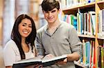 Happy students holding a book in a library Stock Photo - Royalty-Free, Artist: 4774344sean                   , Code: 400-05668949