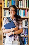 Portrait of a cute student posing with a book in the library Stock Photo - Royalty-Free, Artist: 4774344sean                   , Code: 400-05670297