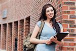 Student posing with a binder outside a building Stock Photo - Royalty-Free, Artist: 4774344sean                   , Code: 400-05670682