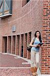 Portrait of a smiling woman with a binder standing outside a building Stock Photo - Royalty-Free, Artist: 4774344sean                   , Code: 400-05670683