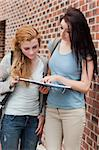 Portrait of a student showing something to her classmate on her notepad Stock Photo - Royalty-Free, Artist: 4774344sean                   , Code: 400-05670693